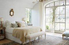 """A headboard was initially planned for the couple's bedroom, but """"we realized we wanted it to be 'less is more,'"""" Brooke says. Keeping with the minimalist feel, soft Belgian linen and a pixie-size gilded mirror balance the rustic yet refined vibe."""