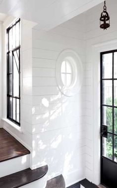 white wood plank walls with nautical peep window and l love the contrast between the dark wood and the white.