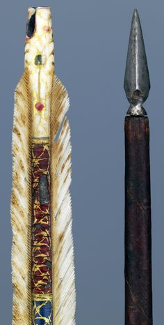 Ottoman arrow, late 16th to early 17th century, cedar shaft?, swatches in red and blue with silver wire, floral and geometric motifs in gold paint, white plumage, about 70 cm (length)  about 25 g (weight). Museum Hessen Kassel.
