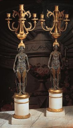A PAIR OF RUSSIAN NEOCLASSICAL ORMOLU AND PATINATED BRONZE FOUR-LIGHT CANDELABRA<br>LATE 18TH/EARLY 19TH CENTURY<br>each with a standing patinated bronze female figure with a tasselled pillow on her head supporting a flared circular candle holder flanked by three spirally fluted candle arms, raised on a circular ormolu-mounted white marble pedestal above a square base.<br>height 37 in. (94 cm.)