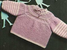 Maglia rasata, punto legaccio, motivo a righe e foretti: usa questi differenti punti di lavorazione e confezione a maglia questo caldo maglioncino in lana per neonato.