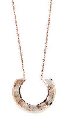 Bronze calcite detailing trims the U-shaped pendant on this Pamela Love necklace. Lobster-claw clasp.