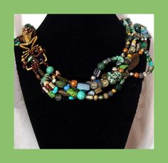 This crazy necklace fits almost like a large torque. Layers of free form beads create a very heavy, firm, unique piece. NOT for the faint of heart. Focal piece is a large bronze frog buckle, woven into the piece. No clasp, slips on over the head. A wonderful piece to welcome in the spring. Approximately 21 inches internal diameter. $50 Free Shipping.  Earrings and/or bracelet available for additional cost.