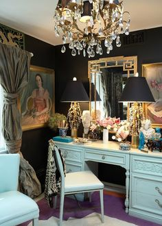 Luxe dressing room - Black walls, crystal chandelier, Italian gilt and crystal lamps with black shades, paintings, gold bamboo mirror, pops of blue
