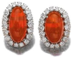 Pair of fire opal and diamond ear clips.     Each set with a cabochon fire opal, within a frame of brilliant-cut diamonds, unsigned, case stamped Gebr, Hemmerle, München.      Sotheby's.