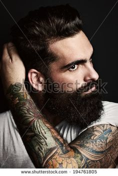 Portrait of handsome bearded man with tattoos - stock photo