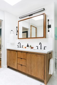 The master bathroom features two electrified medicine cabinets built into a frame designed by me and custom built by my contractor. The light bar is from AllModern and the sconces are from Park Studio.