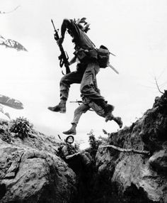 US paratroopers jump over trenches to take their positions around Phouo Vinh Airfield, South Vietnam 13 Jun 65.  Vietnam War