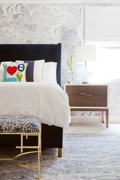 """Cloudy wallpaper in child's room with wood side table, striped lamp, and """"love"""" pillow"""