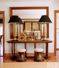 English brass lamps sit on an American harvest table in a traditional entrance hall.