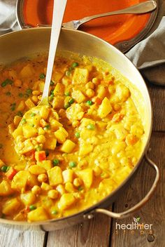 Spicy vegan potato curry with carrots, chickpeas and green peas.