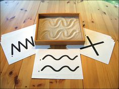 Pre-writing practice. This is a typical Montessori activity - the sand tray - you can also use salt (white or coloured) on the light panel.