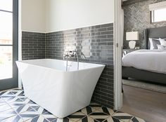 """Bathroom. White and gray master bathroom features upper wall painted in a pale grey and lower wall clad in charcoal gray brick tiles lined with a modern freestanding tub and a wall-mount tub filler atop a white and gray geometric tiled floor.  The tub is a Tiffany 59"""" Small Soaking tub from Wyndham. #bathroom Patterson Custom Homes"""