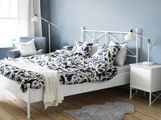Ein Schlafzimmer mit MUSKEN Bettgestell in Weiß, 3-teiligem SÖTBLOMSTER Bettwäsche-Set in Weiß/Blau, MUSKEN Ablagetischen in Weiß und LUDDE Schaffell in Grau