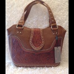 NEW Montana West Tooled Leather Western Bag This handbag features the following: Material: Leather Color:  Brown Closure: Zipper and snap closure Hardware: silver, studded accents, footed bottom Outside features include: Floral and leaf tooled pattern, 1 zippered pocket and one slip pocket.  Inside features include: 2 open compartments sepearated by a zippered pocket. 1 zippered pocket, 2 slip pockets. Montana West signature lining Condition: NWT, absolutely stunning, wonderful leather…