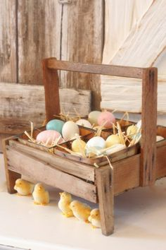 Decorating with a touch of storybook whimsy … little fuzzy chicks find a cozy spot to wait for mama under the berry crate that's filled with sugared Easter eggs.