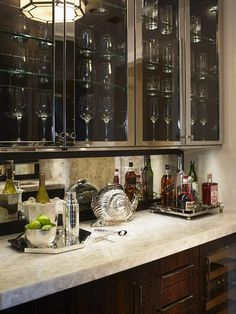 Kitchen bar features stainless steel upper cabinets with glass doors lined with glass shelves filled with wine glasses over cherry stained lower cabinets paired with a white onyx countertop and a mirrored backsplash.