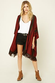 A knit sweater cardigan featuring stripes, tassel trim, short dolman sleeves, open front, and a draped silhouette.