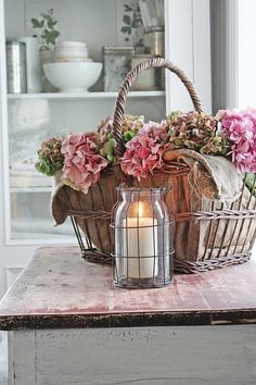 Shabby Chic Burlap Lined Basket Filled with Pink Hydrangea Blossoms with White Candle in Wire Container, and White Shelf with White Dishes in Background, V I B E K E D E S I G N