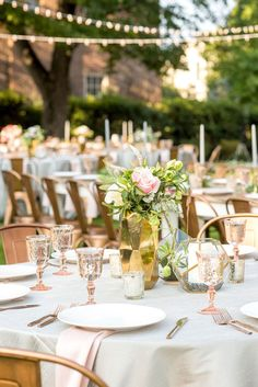 Mikkel Paige Photography pictures from a wedding at Merrimon-Wynne House in Raleigh, NC. Photo of the outdoor reception on the lawn, with round and rectangular farm tables, pink linen napkins, grey plates, and floral centerpieces.