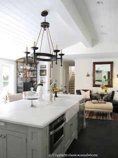 Vaulted wood plank ceiling with center beam.   white cabinets.  kitchen.  home decor and interior decorating ideas.  lake home.