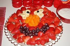 Elmo Fruit Tray  Face: Strawberries without tops  Mouth: Grapes  Nose: Peach or mini-orange slices  Eyes: Banana Slices with Grape in the middle.