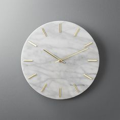 Shop carlo marble and brass wall clock.   Shiny brass hands tell time on smooth, white marble.  Simple, clean design indicates the hour with minimalist dashes instead of numbers.  Elevates the entry or goes glam on a gallery wall.