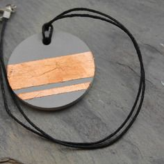 Pendentif rond en béton brut orné de feuille couleur cuivre