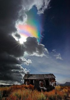 Rainbow colors surround sunspot in clouds over autumn bushes around rustic shack.