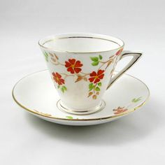 Tea cup and saucer with hand painted orange flowers and gold trimming. Tea cup has a distinctive angular handle. Made by Phoenix China. Excellent condition (see photos). Markings read: Phoenix China T.F & S. Ltd Made in England Please bear in mind that these are vintage items and