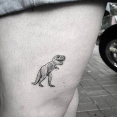 Cute micro T-Rex tattoo on the thigh.