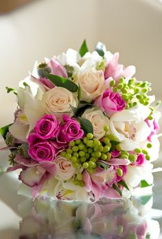 Pink and white roses with orchids and lilies and green hips. Gorgeous pink and white floral bouquet.
