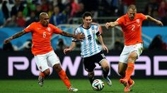 Lionel Messi (C) of Argentina competes for the ball against Nigel de Jong (L) and Ron Vlaar (R) of the Netherlands