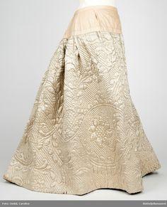 Sannsynligvis av engelsk opprinnelse. Produksjon: 1750 - 1775   Underskjørt i kremgul/ hvit silke. Quiltet/Vattert* med blomstermotiv. http://digitaltmuseum.no/021025813911/?query=caroline%20omlid&sort_by=updated_date&rows=72&pos=47&count=1243