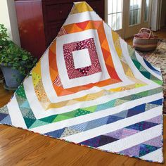 RAINBOW IN A BOX Bright modern lap quilt pattern Designed and machine quilted by GRETCHEN WYLEGALA Immerse yourself in glorious color as you stitch this scrappy asymmetric lap quilt pattern. Rainbow in a Box is made entirely of large half-square triangle units, so piecing is simple and fast. Pattern in the April/May 2016 issue of McCall's Quick Quilts.
