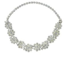 AN ATTRACTIVE DIAMOND NECKLACE FORMING TWO BRACELETS, BY CARTIER   Designed as ten flowerheads with pear-shaped diamond petals and baguette-cut diamond stems to the brilliant-cut diamond neckchain, detachable to wear as two bracelets, I7.5 cm long  Signed Cartier, No. 894439 and with maker's marks for Oscar Heyman & Brothers, No. 504172