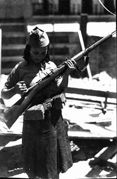 Madrid, julio de 1936. Una miliciana aprende a manejar un maúser, probablemente en el Cuartel de la Montaña. En los primeros seis meses de conflicto, las mujeres accedieron a puestos de combate en las unidades republicanas. Con la creación del EPR, sin embargo, fueron relegadas a puestos de 2a línea. En todo caso, el protagonismo femenino fue mucho mayor en las fuerzas leales que en el bando rebelde, que reservaba a las españolas un papel limitado a ser esposa y madre.