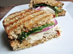 Turkey Caprese Panini  2 slices hearty whole grain bread  1 oz honey goat cheese 1/2 tbsp sun-dried tomato pesto 4 oz turkey meat 1 tbsp thinly sliced red onion 2 tbsp baby spinach leaves  extra virgin olive oil