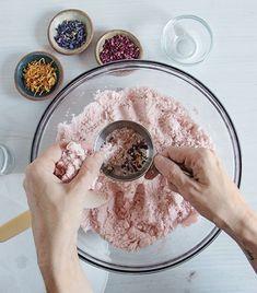 fabriquer ses cosmétiques un bol avec des ingredients pour une boule de bain avec des tasses pleines de petales de fleurs