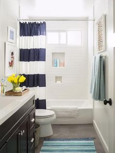 """Since this bathroom is mainly for the boys, I wanted it to be fun but still chic enough for guests,"" says Katrina. So she paired classics like the espresso-hued vanity, slate gray floor tiles, and bleach-white tub tiles with playful accents—a nautically striped West Elm shower curtain and wrapping paper framed as artwork above the towel bar."