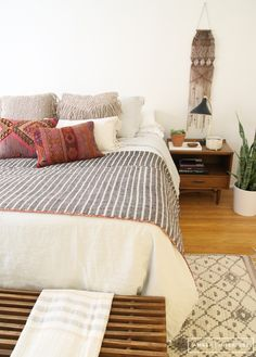 Creamy neutral bohemian bedroom with wall weaving, midcentury nightstand, and styling from Anthropologie