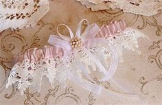 This elegant garter is made of pink blush satin and fine white venise lace. It is embellished with a rose gold and pearl accent and finished off with a double bow of white satin and organza. Your garter comes gift packaged in our signature ivory keepsake box. Measures 2 1/4 inches wide.    ***********SIZING************* I carefully handcraft each garter especially for you. Garters are usually worn 4-6 inches above the knee. To measure, use a soft measuring tape and measure around the exa...