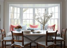 Breakfast Nook. Breakfast nook accented with coral and blue pillows paired with x base dining table surrounded by vintage ladder back chairs flanked by builtin hutches. #BreakfastNook Kerry Hanson Design.