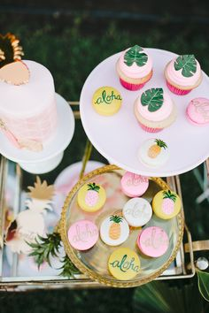"""Cupcakes and macarons from Sweet & Saucy Shop were decked out with edible palm leafs, """"Aloha"""" messages, or painted pineapples. Copy this look when creating a similar dessert bar, or ask your baker to incorporate these elements on your wedding cake."""