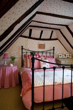 Red gingham check on bed in attic conversion of timber framed cottage  Grafty Green  Kent  England