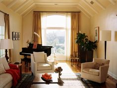 Floor-to-ceiling windows allow lots of natural light to pour into this elegant cream-colored living room. White ceiling beams add architectural interest and emphasize the room's height.  Neutral furnishings, a traditional rug, full-length gold drapes and the baby-grand piano add to the room's sophisticated, timeless look.  Design by Kristi Nelson.