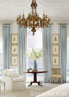 Love the blue window treatments - simplistic but elegant -  & gold chandelier! I also like the way they placed the wall prints between windows. ~ 10 Ways to Create a Calming Space in 2016