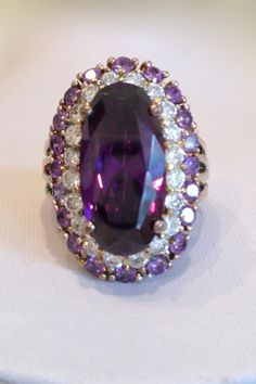 Oval Cut Center Stone in Amethyst CZ Encircled By a Row of Clear CZ's and a Row of Amethyst CZ