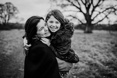 Mother and daughter laughing together in a field in Kildare during a family photo session with Lorraine Maguire Photography
