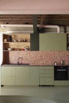 Pink-toned terrazzo tile counters and a backsplash and olive green-painted cabinetry enlivens the kitchen, where the designers created open shelving using leftover plywood from the mezzanine ceiling panels. Green Kitchen Cabinets, Open Cabinets, Kitchen Tile, Kitchen Modern, Melbourne Pubs, Küchen Design, Interior Design, Design Trends, Design Ideas